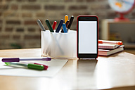Smartphone on wooden table in children's room - MFF001410