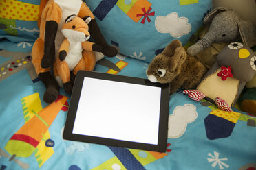 Tablet computer and soft toys on bed in children's room - MFF001412