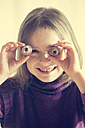 Smiling little girl holding two lychees in front of her eyes - SARF001293