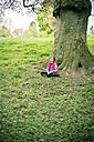 Little girl sitting in front of an old tree on a meadow - SARF001294