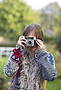 Young woman taking a picture of viewer with an old camera - WWF003889