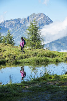 Austria, Altenmarkt-Zauchensee, young woman hiking in alpine landscape - HHF005071