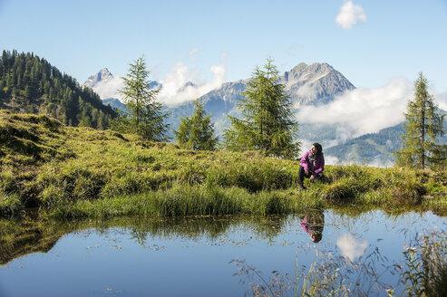 Austria, Altenmarkt-Zauchensee, young woman hiking in alpine landscape - HHF005073