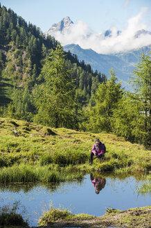 Austria, Altenmarkt-Zauchensee, young woman hiking in alpine landscape - HHF005076