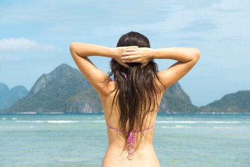Philippines,Palawan, El Nido, woman with hands behind her head at Las Cabanas beach - GEMF000066