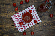 Glass of tomato juice and tomatoes on kitchen towel - LVF002709