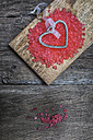 Metal heart with pink jelly on wooden chopping board - MGOF000049