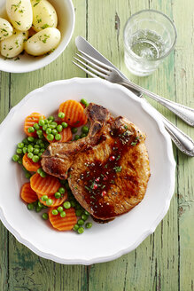 Pork chop with carrots, peas and boiled potatoes on plate - KSW001385