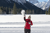 Austria, Tyrol, Pertisau, young woman throwing snowball - MKFF000159