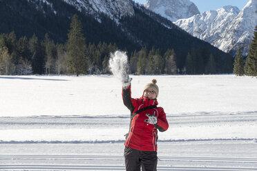 Austria, Tyrol, Pertisau, young woman throwing snowball - MKFF000159