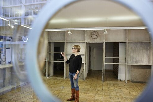 Woman standing in empty shop holding cell phone - EDF000118