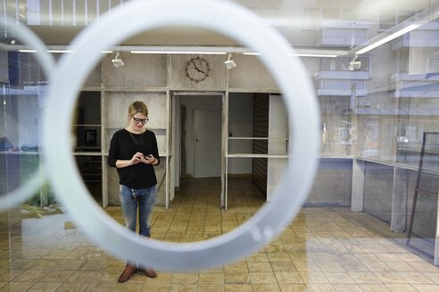 Woman standing in empty shop holding cell phone - EDF000122