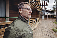 Mature man in front of wooden building structure - MFF001421