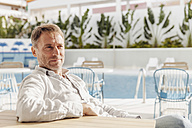 Spain, Canary Islands, Gran Canaria, mature man sitting by the pool - MFF001444
