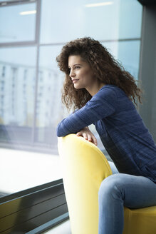 Smiling young woman looking out of window - RBF002313