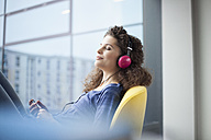 Young woman wearing headphones at the window - RBF002322