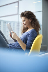 Smiling young woman using digital tablet at the  window - RBF002328