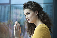 Smiling young woman looking out of window - RBF002334