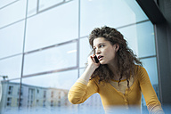 Frightened young woman on the phone at the window - RBF002340