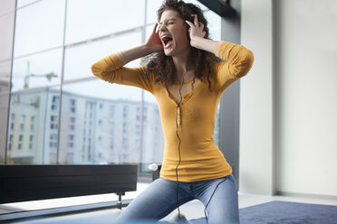 Screaming young woman wearing headphones at the window - RBF002342