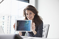 Portrait of smiling young woman at desk holding digital tablet - RBF002350