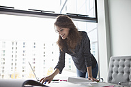 Young woman using laptop at desk in office - RBF002353
