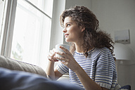 Smiling young woman with cup of coffee looking out of window - RBF002362