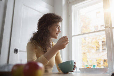 Young woman at table eating from cereal bowl - RBF002271