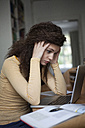 Overstressed young woman with laptop in home office - RBF002274