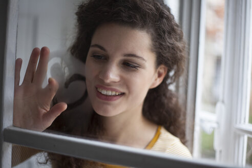 Smiling young woman painting heart on windowpane - RBF002280
