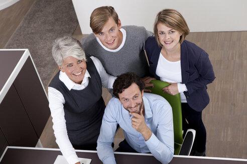 Smiling business team at desk in office - MFRF000015