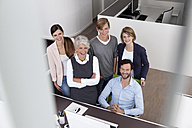 Happy business team at desk in office - MFRF000021