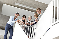 Businesspeople using cell phones in staircase - MFRF000055