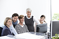 Smiling business team working on computer in office - MFRF000025