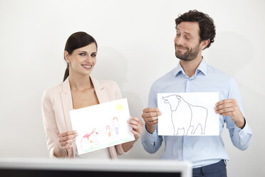 Businesswoman holding child's drawing and businessman holding paper with bull figure - MFRF000030