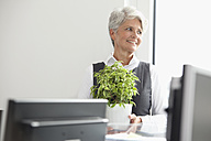 Smiling mature businesswoman in office looking away - MFRF000012