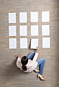 Businesswoman sitting on floor organizing blank sheets of paper - MFRF000042