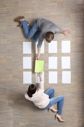 Businessman and businesswoman sitting on floor organizing blank sheets of paper - MFRF000045