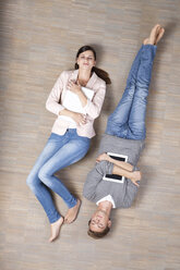 Man and woman lying on floor with laptop and digital tablet - MFRF000048