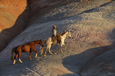 USA, Wyoming, cowgirl with two horses in badlands - RUEF001438