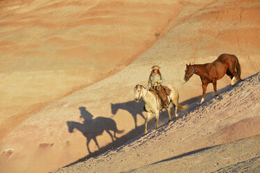 USA, Wyoming, cowgirl with two horses in badlands - RUEF001441