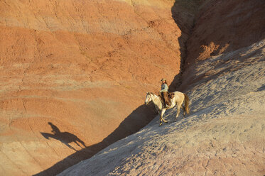 USA, Wyoming, cowgirl riding in badlands at twilight - RUEF001442