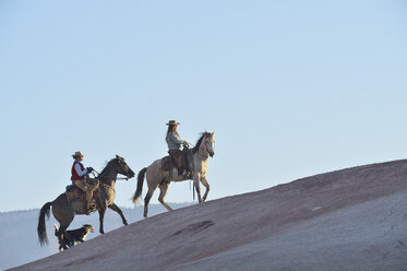 USA, Wyoming, two riding cowgirls and their dog in badlands - RUEF001446