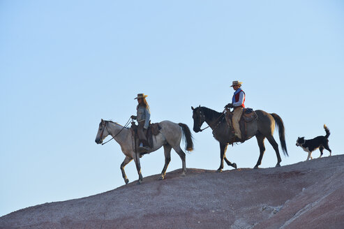 USA, Wyoming, two riding cowgirls and theit dog in badlands - RUEF001447