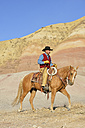 USA, Wyoming, cowboy riding in badlands - RUEF001465