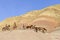 USA, Wyoming, cowboys and cowgirl herding horses in badlands - RUEF001486