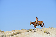 USA, Wyoming, cowboy riding in badlands - RUEF001507