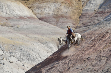 USA, Wyoming, cowboy riding downwards in badlands - RUEF001511