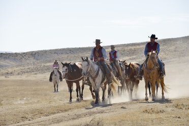 USA, Wyoming, cowboys and cowgirl leading horses in badlands - RUEF001512