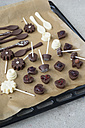 Homemade pralines and chocolate lollies on baking paper - MYF000873